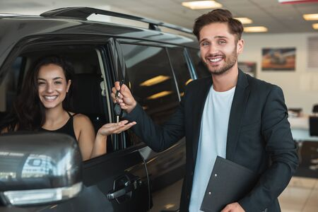 handsome man manager gives car keys to beautiful brunette woman client after succesful retail deal in dealership center standing near new SUV Stock fotó