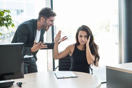 strikte baas die vloekt op overstuur vermoeide werknemervrouw voor slecht werk op de werkplek die boos kijkt