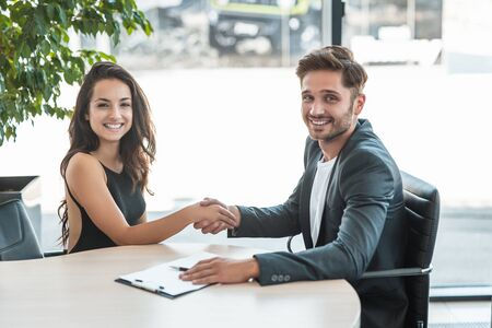 beautiful young woman manager shaking hands with handsome man client after holding succesful business purchase deal at the office Foto de archivo