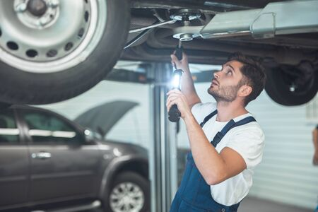 young handsome mechanic working in car service department fixing vehicle chassis Stockfoto