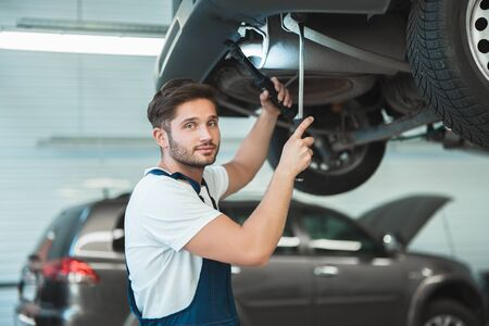 young handsome mechanic working in car service department fixing the problem in vehicle chassis