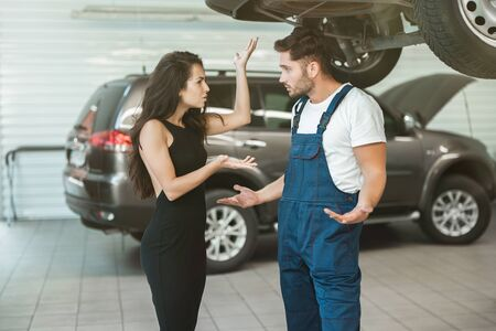 beautiful woman client is complaining about bad service provided by mechanic in car damage department