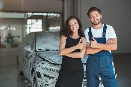 young handsome man wearing uniform and beautiful woman client standing in car wash station showing like signs Stockfoto