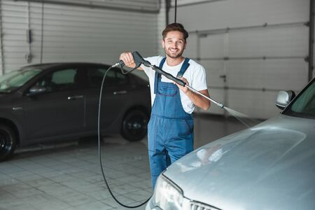 young handsome man wearing uniform washing car at car washing station using high pressure water looks happy