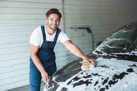 young handsome smiling man wearing uniform washing car with sponge at car washing station