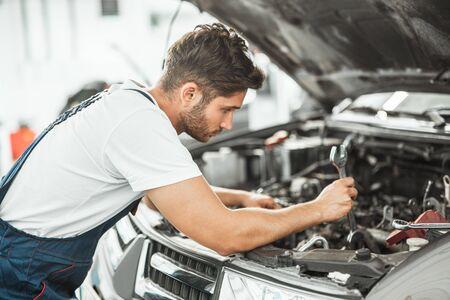 junger lächelnder, gutaussehender Mechaniker in Uniform, der Motorprobleme in der Motorhaube repariert, die im Servicecenter arbeitet