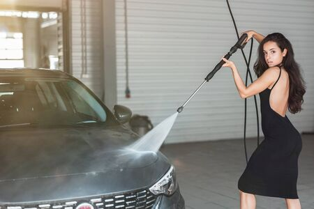 young beautiful woman in black dress washing car at car washing station using high pressure water Stock Photo