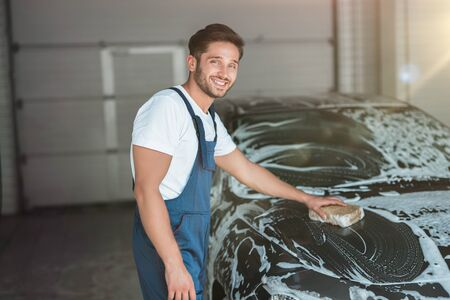 young handsome man wearing uniform washing car with sponge at car washing station Stock Photo