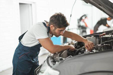 young handsome smiling mechanic in uniform fixing motor in car bonnet working in service department