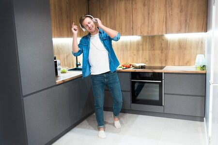young handsome man in headphones listening to music and dancing while cooking in the kitchen Archivio Fotografico - 132229425