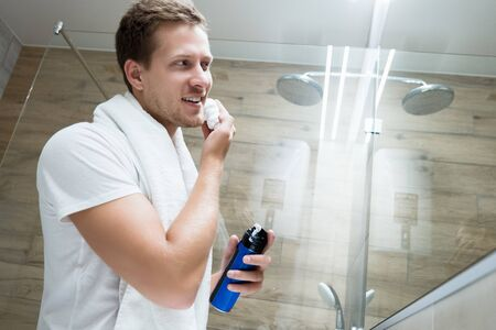 young handsome smiling man with white towel on his shoulders looking in the bathroom mirror applying shaving foam on his face Stok Fotoğraf