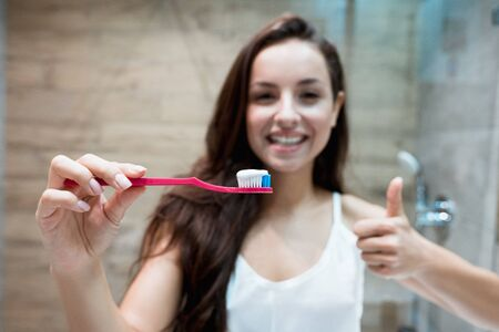 young beautiful smiling woman holds tooth brush with tooth paste in the bathroom showing like sign