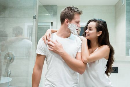 young couple handsome man and beautiful smiling woman hugging in bathroom while he has shaving foam on his face