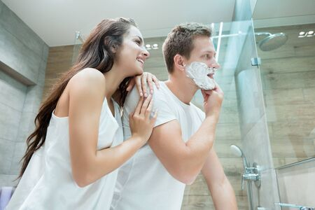 young couple handsome man and beautiful woman looking in bathroom mirror while he applies shaving foam on his face