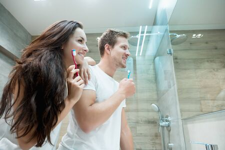 young couple handsome man and beautiful woman looking in bathroom mirror while brushing their teeth