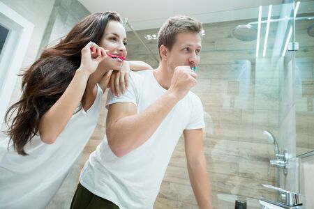 young couple handsome man and beautiful brunette woman looking in bathroom mirror while brushing their teeth Stok Fotoğraf