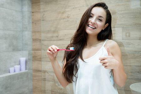 young beautiful woman standing in front of bathroom mirror while brushing her teeth showing like sign