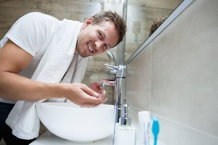 young handsome smiling man rinses his face with water in bathroom
