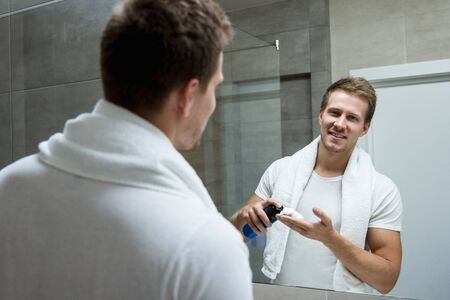 young handsome smiling man with white towel on his shoulders looking in the bathroom mirror putting shaving foam on his hand Stok Fotoğraf