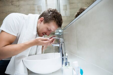 young handsome man rinses his face with water in bathroom.
