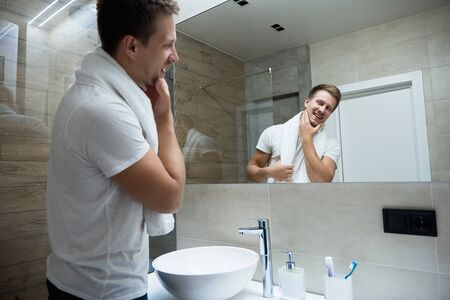 young handsome smiling man with white towel on his shoulders looking in the bathroom mirror Фото со стока