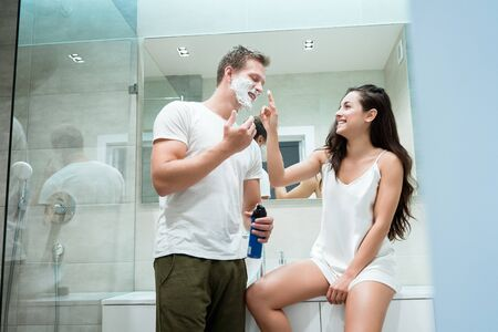 young handsome man and beautiful woman having fun in bathroom while he applies shaving foam