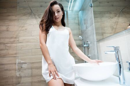 young beautiful sexy woman in white gown standing in the bathroom while doing her morning routine Stok Fotoğraf