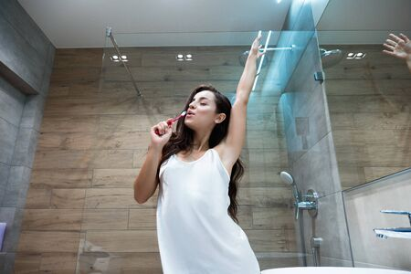 young beautiful smiling woman in white gown holds tooth brush like a microphone and sings in the bathroom while doing her morning routine