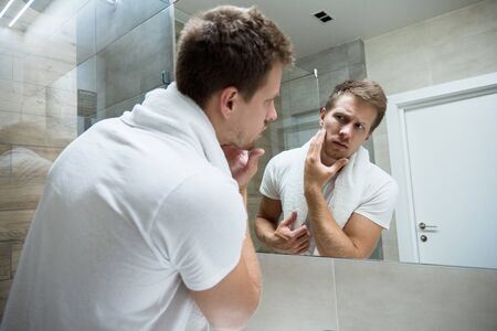 young handsome man with white towel on his shoulders looking in the bathroom mirror touching his face