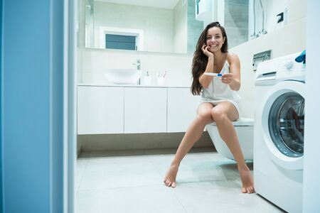 young beautiful woman sits on the toilet bowl holding pregnancy test feeling happy Reklamní fotografie - 132229922