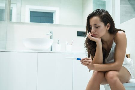 young beautiful woman sits on the toilet bowl after doing pregnancy test feeling upset