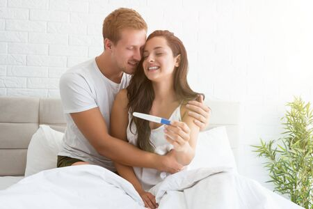 young man is happy hugging beautiful smiling woman when she shows him pregnancy test while both are sitting in bed