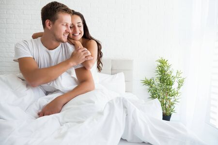 young couple handsome man and beautiful brunette woman hugging each other in bed in bright bedroom feeling happy