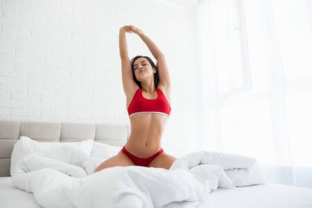 young beautiful woman in red underwear stretching in bed in bright bedroom Stock fotó