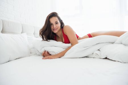 young attractive woman in red sexy underwear lying in bed in bright bedroom smiling Stock fotó