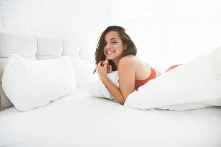 young attractive happy woman in red sexy underwear lying in bed in bright bedroom smiling