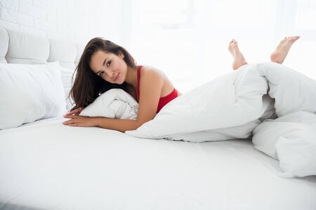 young attractive woman in red underwear lying in bed in bright bedroom looking sexy