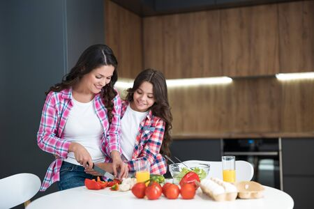 young beautiful brunette woman and her cute daughter cooking breakfast cutting red pepper in the kitchen looking happy