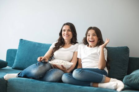 beautiful young mother with her cute teenager daughter watching exciting movie on the sofa eating popcorn Banque d'images - 132230971
