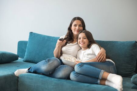beautiful young mother with her cute teenager daughter watching exciting film on the sofa eating popcorn Stock fotó