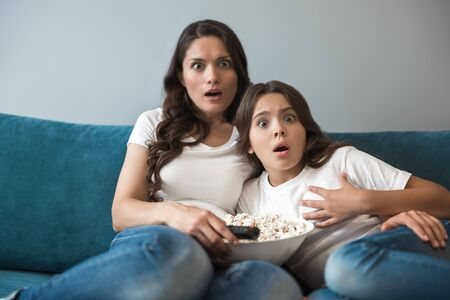 beautiful young mother with her cute teenager daughter watching horror movie on the sofa eating popcorn looking scared Banque d'images - 132231455