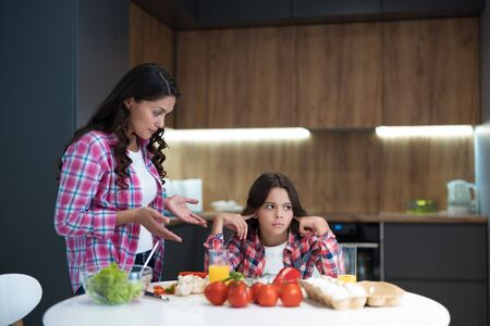 young beautiful woman having fighting with her teen daughter during cooking in kitchen looking upset