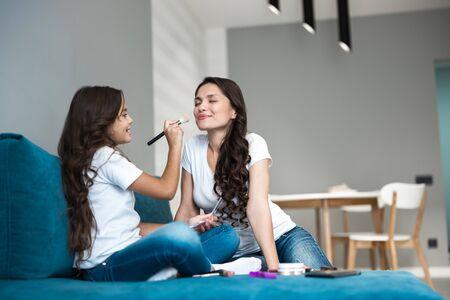 jolie fille adolescente appliquant de la poudre libre sur le visage de sa jeune belle mère avec un pinceau à maquillage
