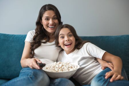 beautiful young mother with her cute teenager daughter watching entertainment tv program on the sofa eating popcorn