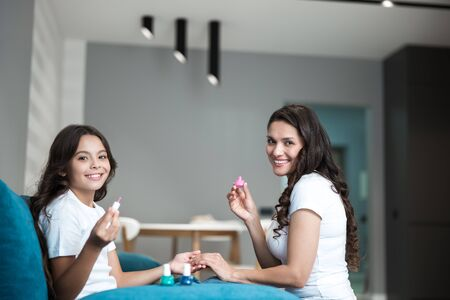beautiful young mother and her cute smiling teen daughter doing manicure applying nail polish both having fun