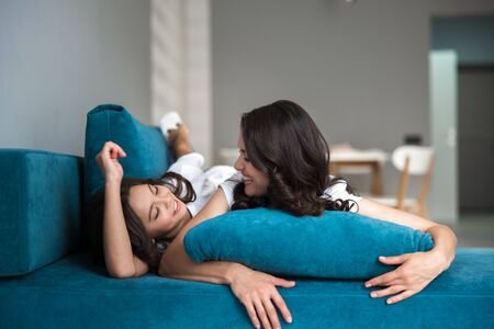 beautiful young mother and her cute teen daughter having fun on the sofa both smiling Foto de archivo - 132231712