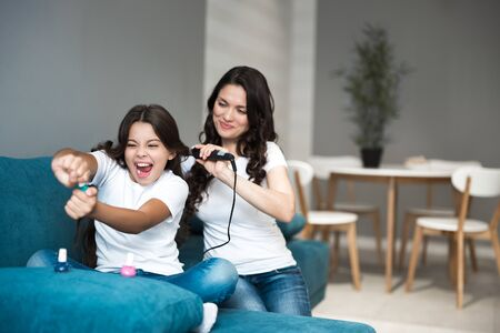 beautiful young mother with her cute teen daughter having beauty day applying nail polish and curling hair using curler both looking happy Stok Fotoğraf