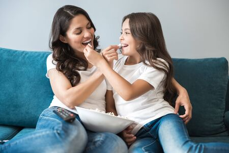 mother and daughter share each other popcorn while watching cartoon on the sofa