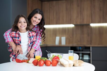 cute teenager girl helping her beautiful mother to cook breakfast in the kitchen looking happy Stock Photo