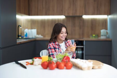 cute teen daughter drinking orange juice for breakfast in the kitchen looking happy